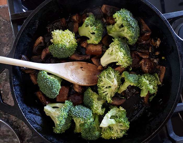 Cooked Portobello mushrooms and broccoli in a skilet