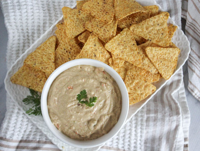 An overhead view of queso dip in a bowl on a try with chips
