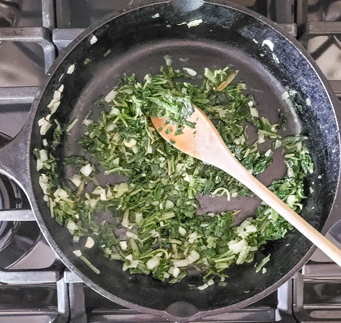 spinach, garlic and onions cooking in a skillet