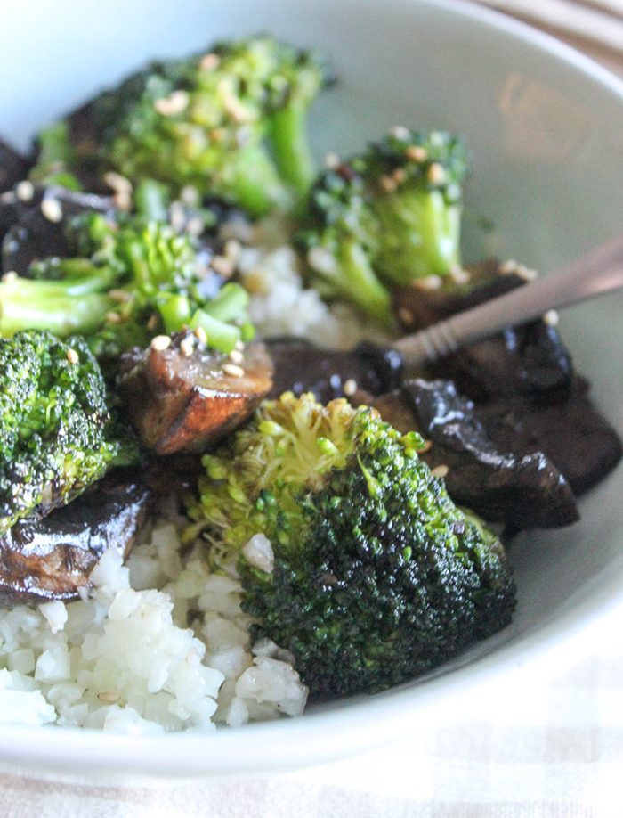 a close up of broccoli and mushrooms in a dish