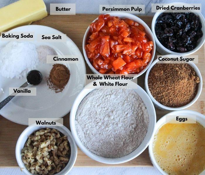 an overhead view of the ingredients: vanilla, cinnamon, baking soda sea salt, butter, persimmon pulp, dried cranberries, coconut sugar, eggs, flour, walnuts