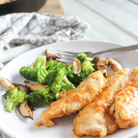 healthy orange chicken on a plate with broccoli and mushrooms
