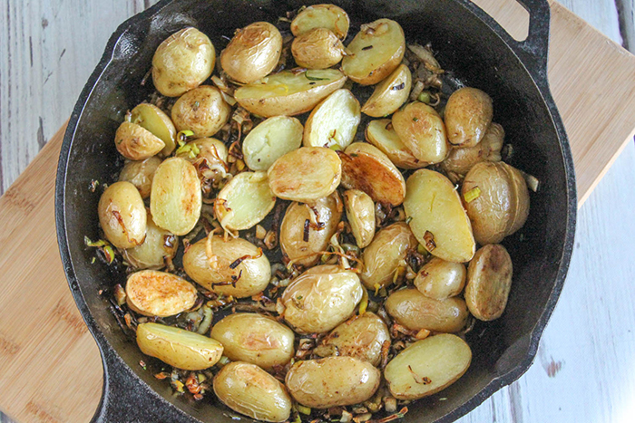 an overhead view of the potatoes mixed in the skillet with the caramelized leeks and garlic.
