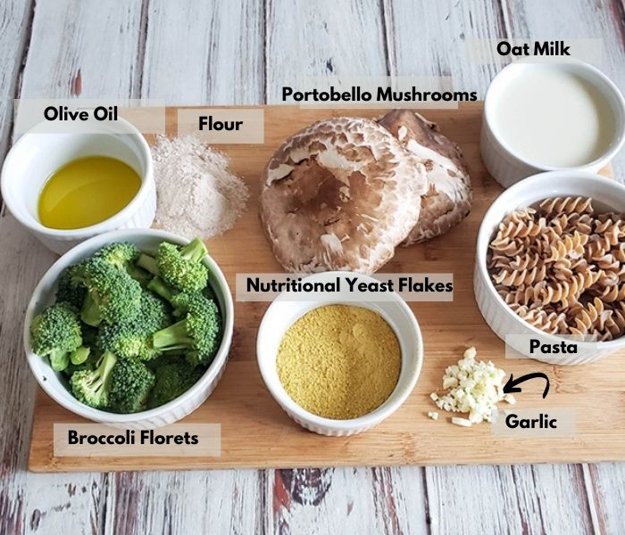 vegan mac and cheese ingredients on a cutting board: olive oil, flour, mshrooms, milk, broccoli, nutritional yeast, garlic and pasta