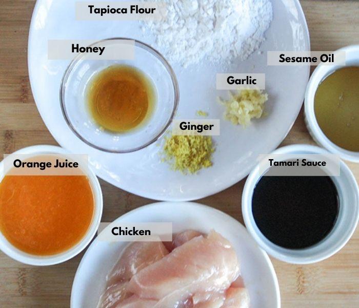 the ingredietns on a board: Clockwise: orange juice, honey, tapicoa flour, sesame oil garlic ginger, tamari sauce, chicken tenders