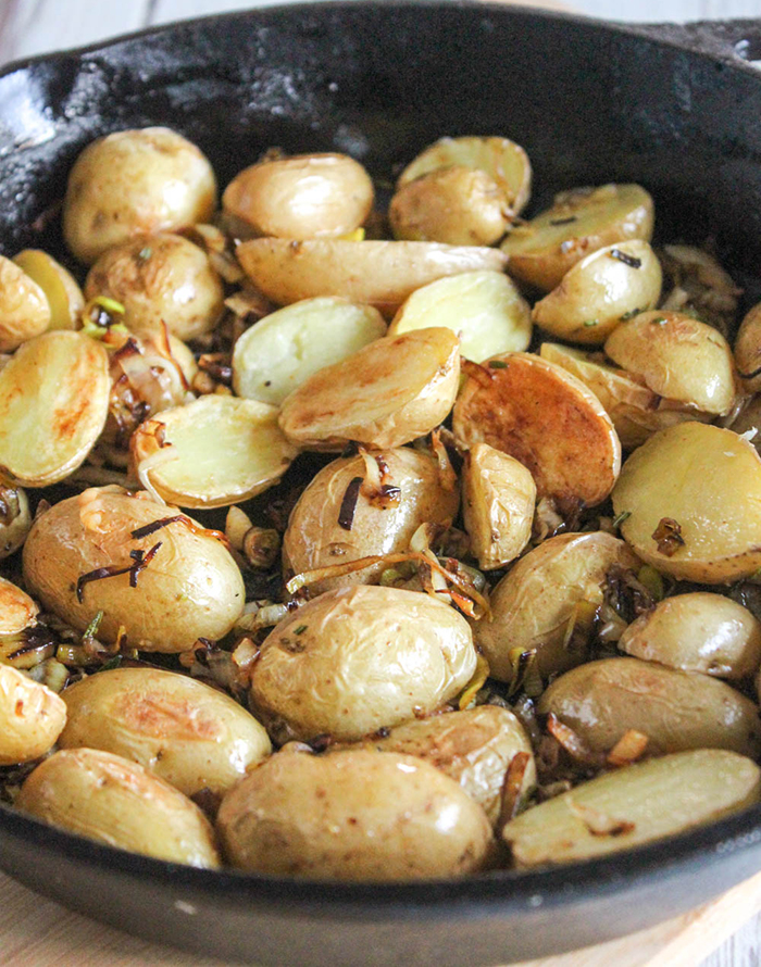 a close up of the potatoes in a skillet with the caramelized leeks