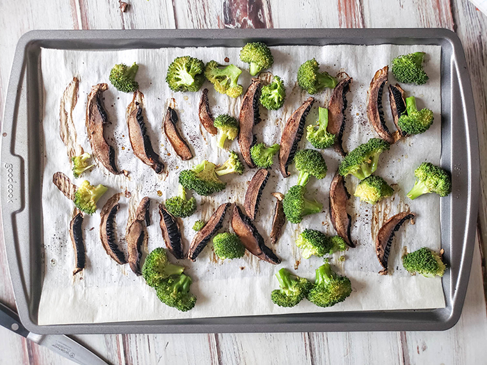 sliced mushrooms on a baking tray with broccoli