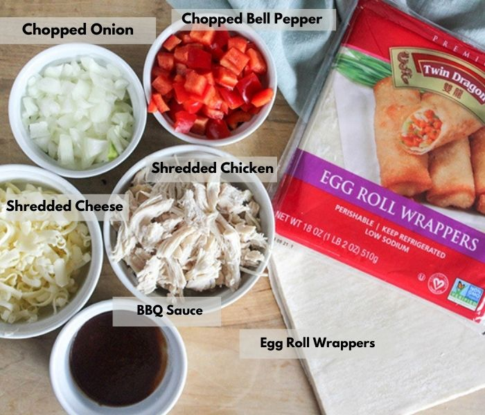 The ingredients on a cutting board: BBQ sauce, cheese, chicken, peppers, onions, egg roll wrappers
