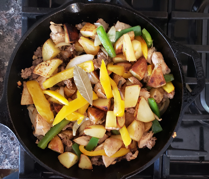 an overhead view of the chicken, sausage and broth added to the skillet with a bay leaf on top