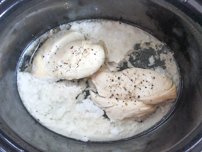 two cooked chicken breasts in a crockpot