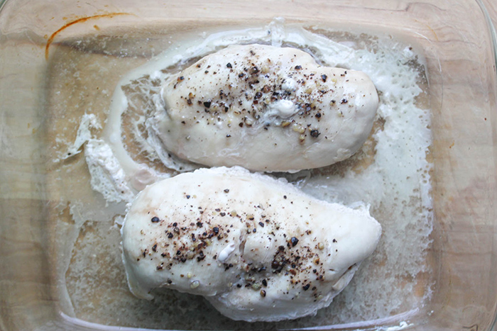 two cooked chicken breasts in a baking dish