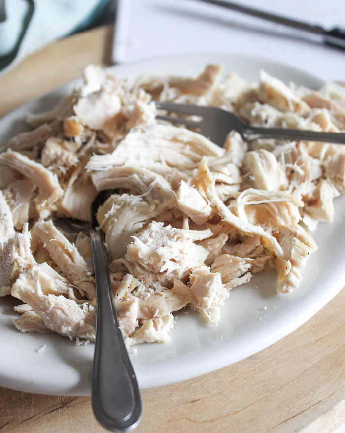 shredded chicken on a white plate with two forks