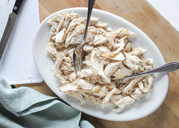 shredded chicken on a plate with two forks.