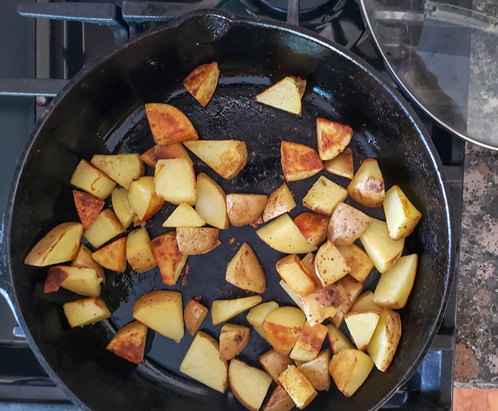 an overhead view of potato chunks cooking in a skillet