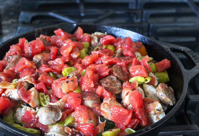 All of the ingredients in a skillet topped with tomatoes