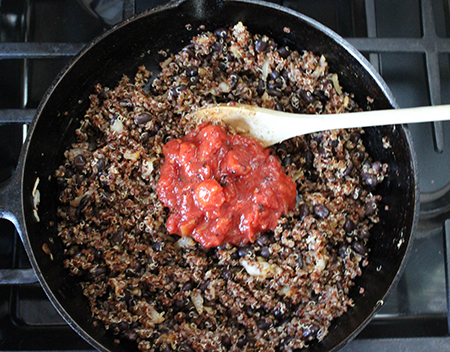 tomatoes, onions, on top of quinoa and beans in a pan