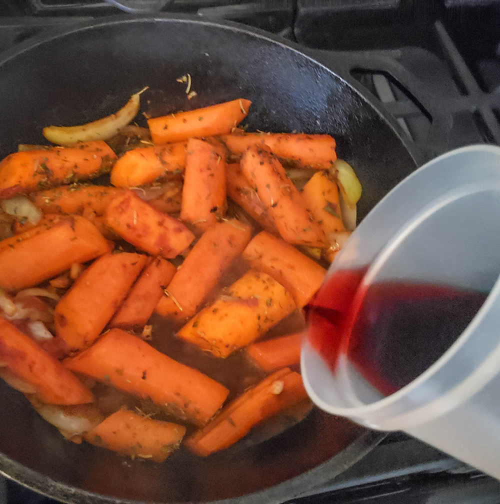 carrots and onions in a skillet with wine pouring in