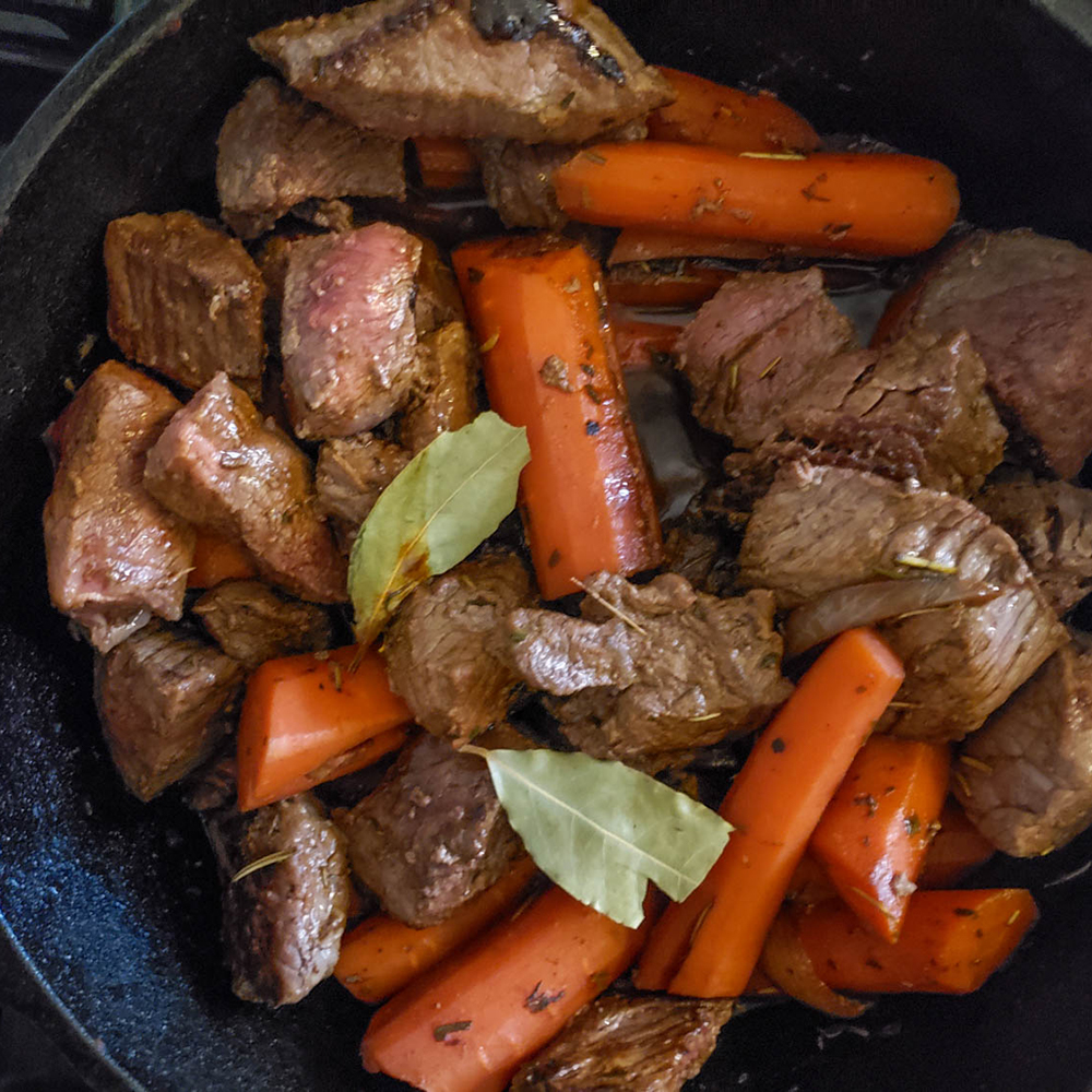 an overhead view of stew (beef, carrots, bay leaves) in a skillet ready to put in the oven