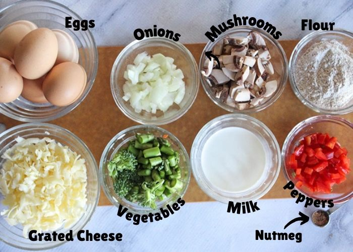 Ingredients fro the breakfast pie: shredded cheese, eggs, vegetables, onions, mushrooms, milk, peppers and flour