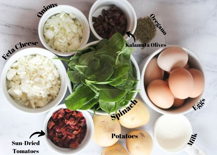 Mediterranean quiche ingredients: sun-dried tomatoes, feta cheese, onions, olives, oregano, eggs, milk potatoes and spinach