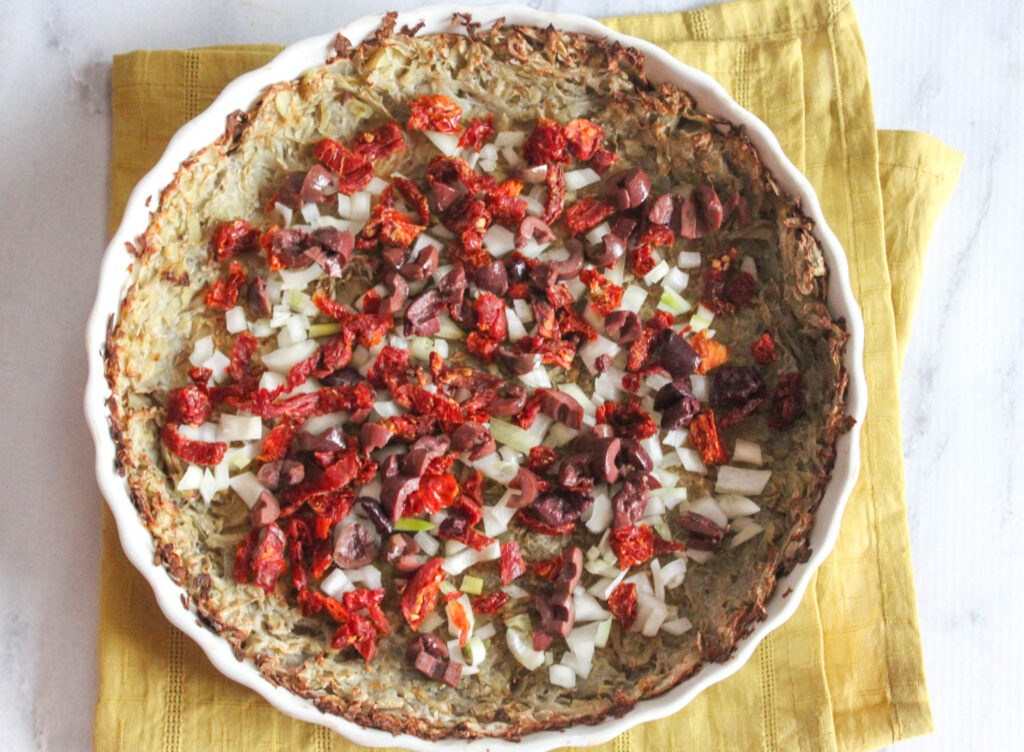 an overhead view of sun-dried tomatoes olives and onions on top of the potato crust