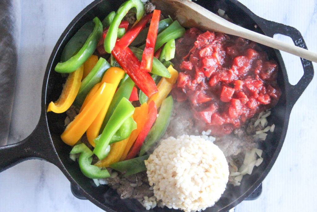 cooked brown beef in a pan with rice, peppers and tomatoes