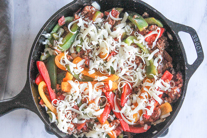 deconstructed peppers in a skillet with shredded cheese on top