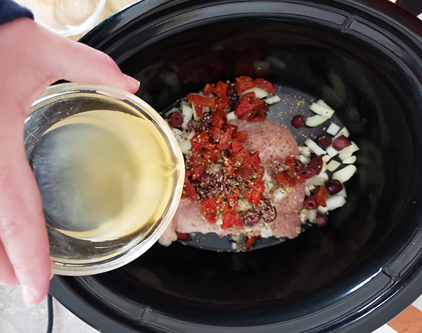 pouring broth onto the chicken with tomatoes, onions olives