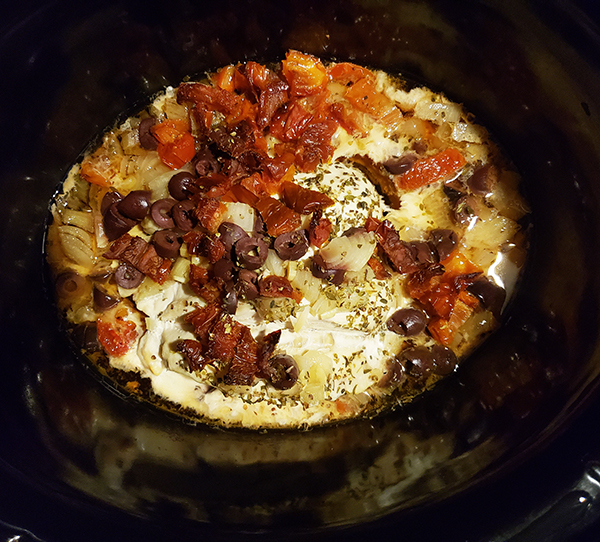 the cooked and completed chicken in a crockpot.