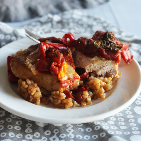 a pork chop covered with tomatoes, peppers and seasoning cut in half on top of rice.