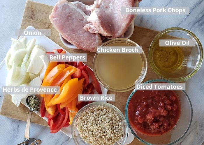 ingredients for pork chop casserole on a cutting board: rice, herbs de provence, bell peppers, onion, pork chops, chicken broth olive oil, diced tomatoes
