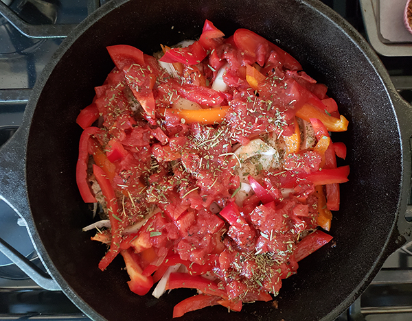 pork chops in a skillet topped with tomatoes and seasoning