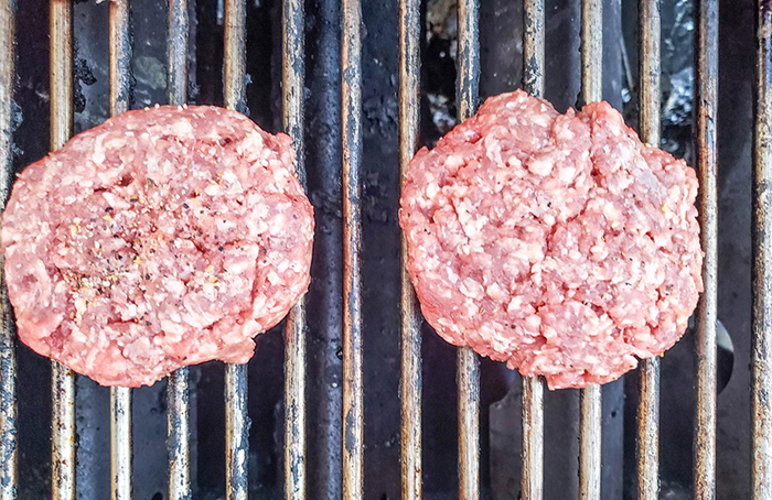 two raw hamburgers on a grill