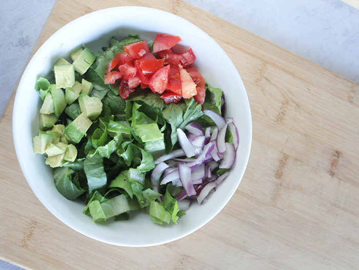 lettuce tomatoes, onions, avocado in a bowl