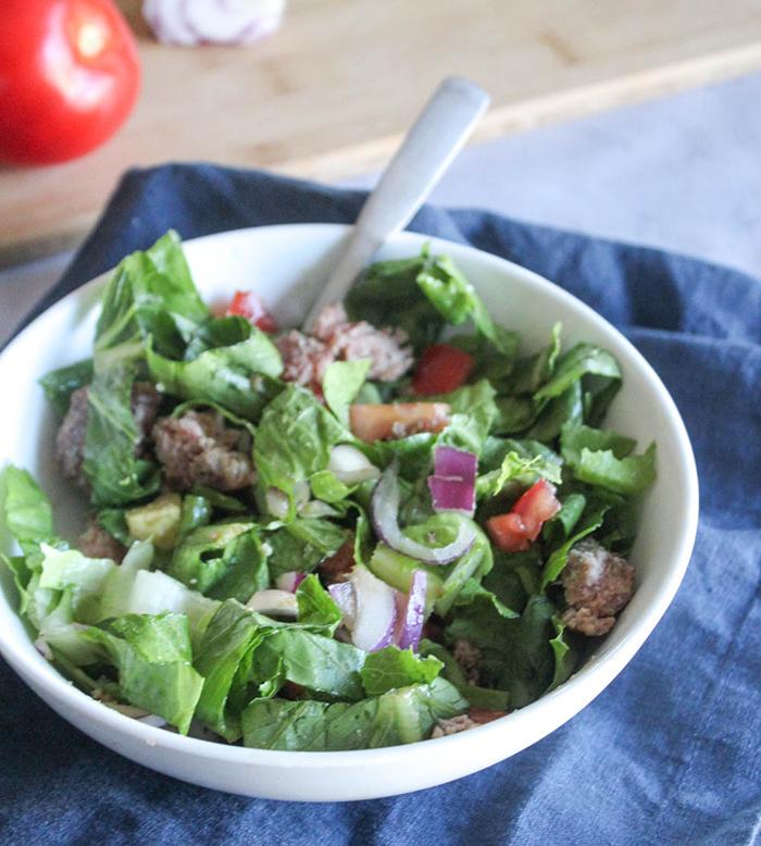 a bowl of lettuce, chopped up hamburger, onions avocado and tomatoes