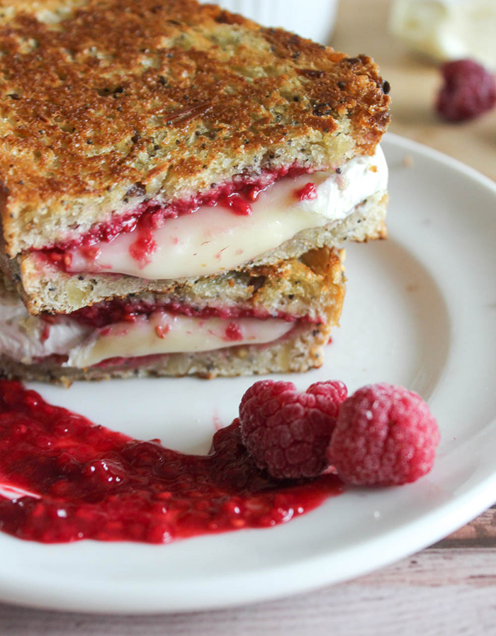 grilled brie cheese with raspberries sandwich on a plate