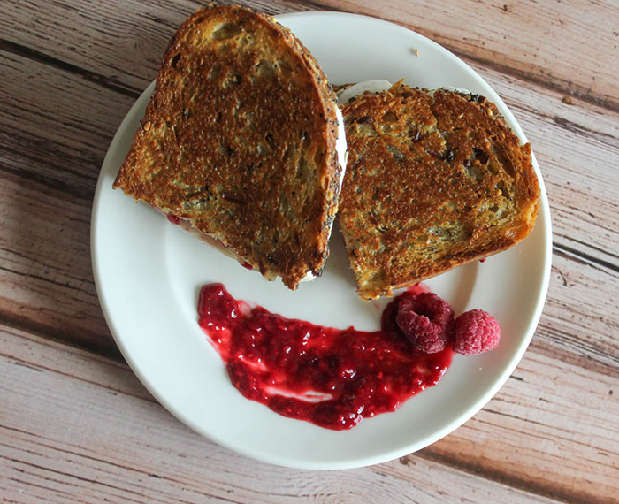 an overhead shot of grilled brie cheese with raspberry sauce on the side