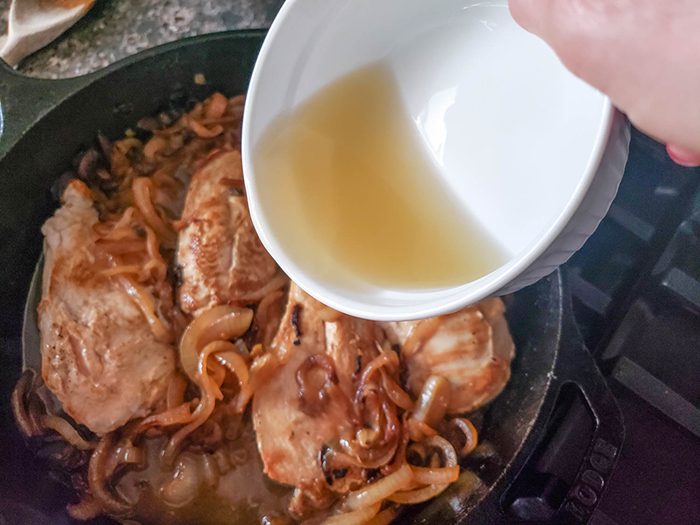 chicken broth pouring into a skillet