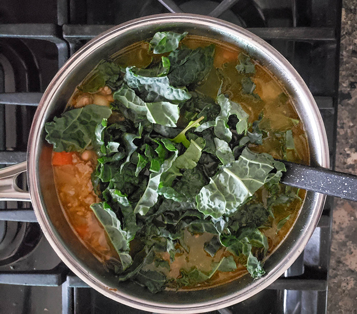 a pot of soup with fresh kale on top