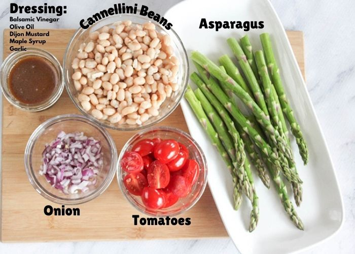 asparagus salad ingredients: asparagus, tomaotes, onion, dressing, white beans on a cutting board.