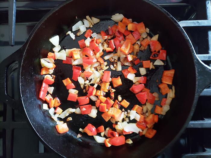 peppers and onions cooking in a skillet