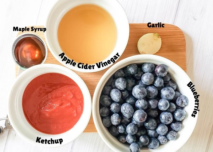 the ingredients on a cutting board, ketchup, maple syrup, Apple Cider Vinegar, garlic, blueberries