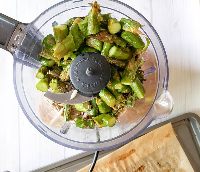 chopped asparagus garlic and sunflower seeds in a food processor