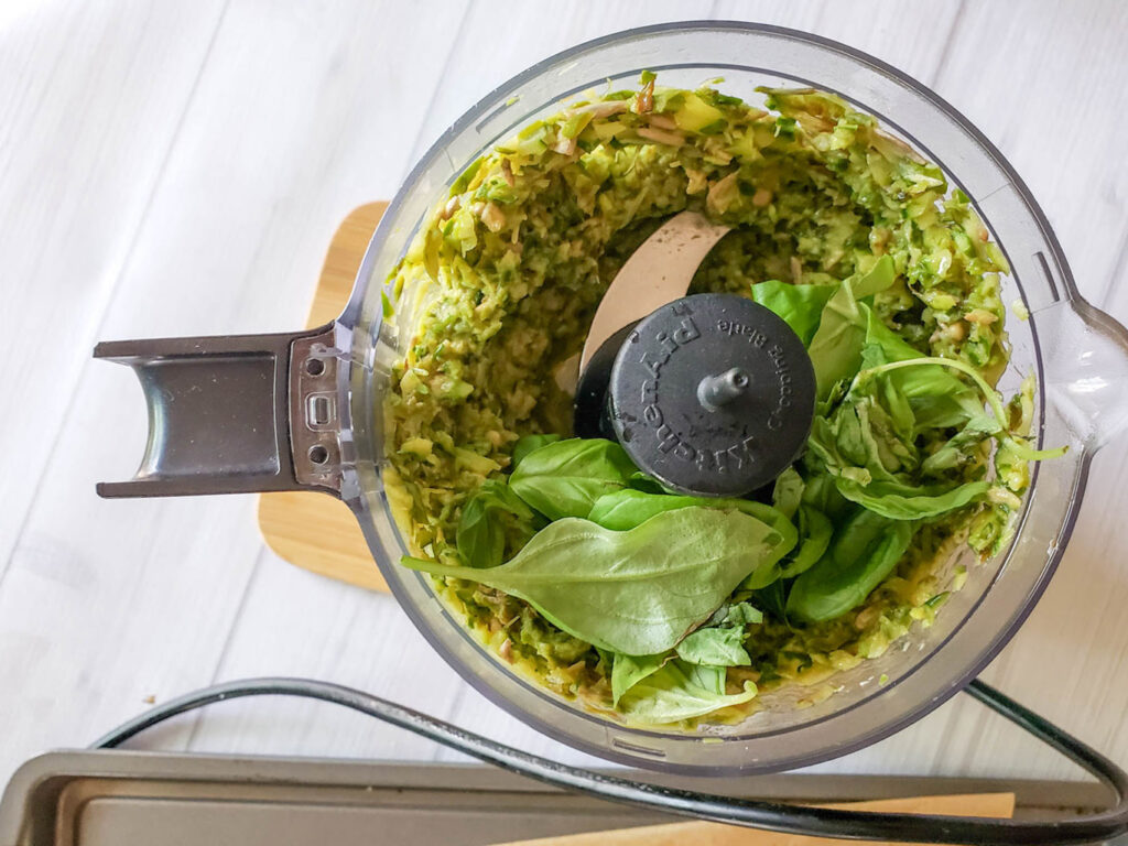 pesto mixture with basil in a food processor