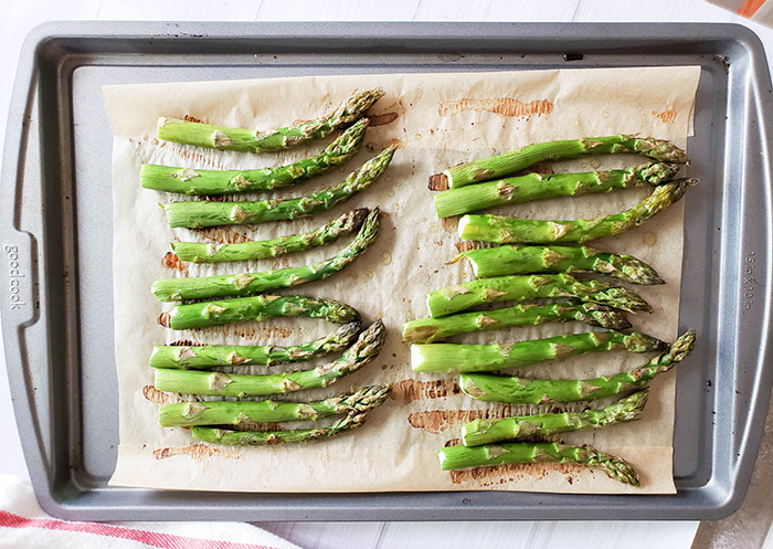 roasted asparagus arranged on a baking sheet with oil
