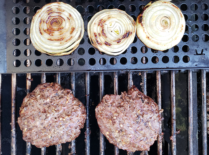 three onion slices and two burgers cooking on a grill