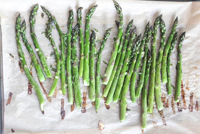 A view of fully roasted asparagus on parchment paper