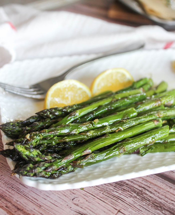 a close up of roasted asparagus spears on white plate with lemon wedges