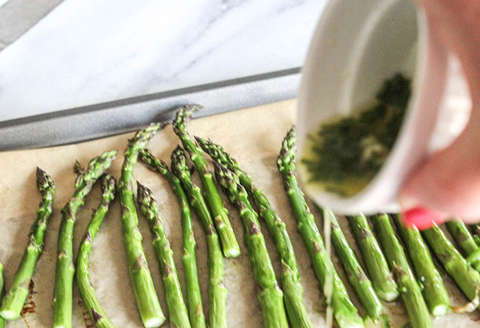 pouring the melted butter over the asparagus