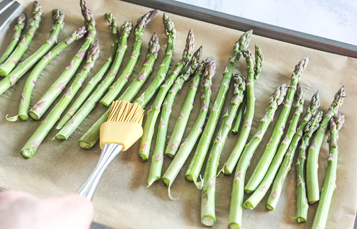 brushing oil onto raw asparagus with a basting brush